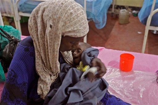 Asiah Dagane holds Mihag Gedi Farah, her seven month old child with a weight of 7 pounds, 8 ounces (3.4 kilograms) at a field hospital of the International Rescue Committee, IRC, in the town of Dadaab, Kenya, Tuesday, July 26, 2011.  (AP)