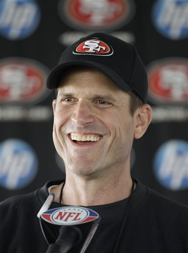 San Francisco 49ers coach Jim Harbaugh answers a question at a new conference.