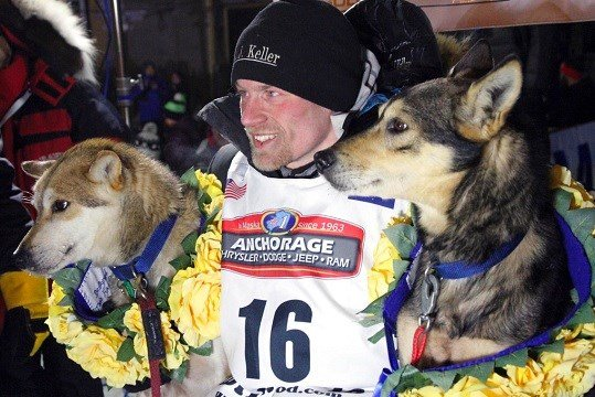 Dallas Seavey poses with his lead dogs Reef, left, and Tide after finishing the Iditarod Trail Sled Dog Race in Nome, Alaska.