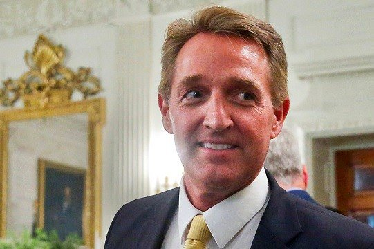 Sen. Jeff Flake, R-Ariz. walks to his seat as he attends a luncheon with other GOP Senators and President Donald Trump.