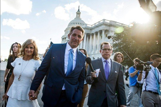 Sen. Jeff Flake, R-Ariz., accompanied by his wife Cheryl, leaves the Capitol in Washington.