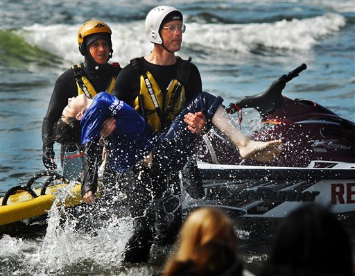 Surf rescue swimmer Doug Knutzen carries Dale Ostrander to the shore of the Cranberry Rd. beach approach Aug. 5, 2011, in Long Beach, Wash. (AP Photo/Damian Mulinax/Chinook Observer)
