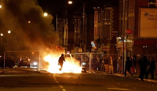 A rioter walks through a burning barricade in the Toxteth area of Liverpool on Wednesday August 10, 2011. In the northern city of Liverpool, about 200 youths hurled missiles at police in a second night of unrest. (AP Photo/PA, Peter Byrne)