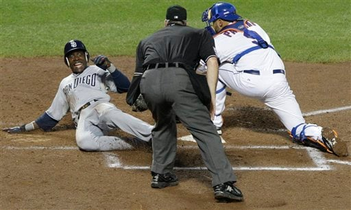 San Diego Padres' Orlando Hudson slides past New York Mets catcher Ronny Paulino to score on an Aaron Cunningham single as umpire Bill Welke looks on during the fourth inning of a baseball Tuesday, Aug. 9, 2011, in New York. (AP Photo/Frank Franklin)