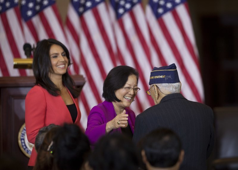Celestino Almeda, a Filipino World War II veteran, is congratulated by Sen. Mazie Hirono, D-Hawaii, and Rep. Tulsi Gabbard, D-Hawaii, during a ceremony at the Emancipation Hall on Capitol Hill in Washington.