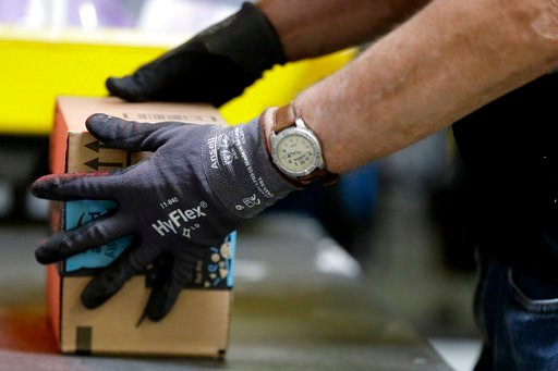 FILE - In this Tuesday, Aug. 1, 2017, file photo, an employee packages a product at the Amazon Fulfillment center in Robbinsville Township, N.J. (AP Photo/Julio Cortez, File)