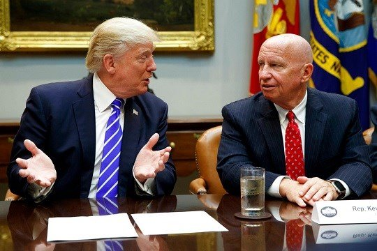 Rep. Kevin Brady, R-Texas, right, listens as President Donald Trump speaks during a meeting with members of the House Ways and Means committee.