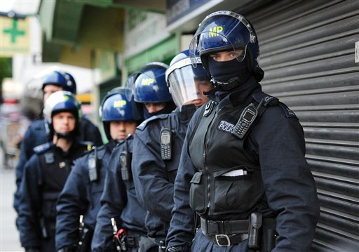 Metropolitan Police officers prepare to carry out a raid on a property on the Churchill Gardens estate in Pimlico, London during an operation where police hope to recover property stolen during the recent disturbances in the capital Thursday Aug. 11, 2011