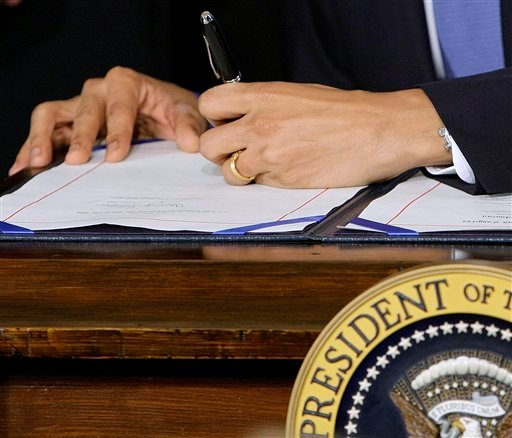 In this March 23, 2010, file photo President Barack Obama signs the health care bill in the East Room of the White House in Washington. (AP Photo/J. Scott Applewhite, File)