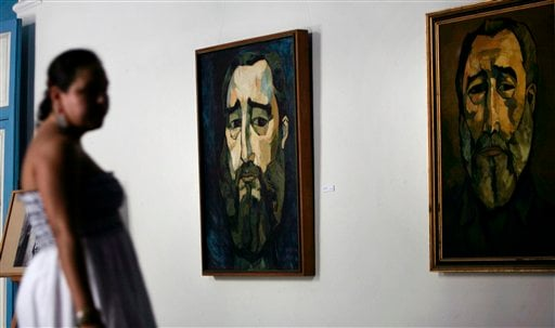 A woman attends an exhibit of paintings depicting Cuba's leader Fidel Castro by late Ecuadorian painter Oswaldo Guayasamin in Havana, Cuba, Friday, Aug. 12, 2011. Artists and admirers of ailing Fidel Castro celebrate his 85th birthday starting Friday.