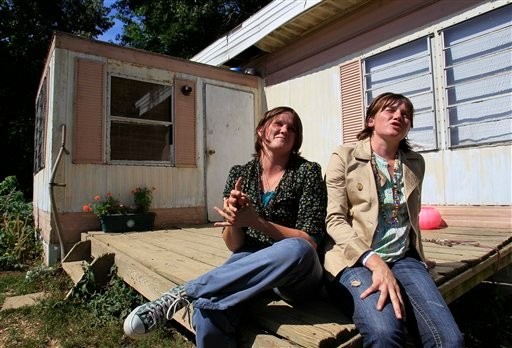 In this Aug. 12, 2011 photo, Stephanie, left, and Raechel Schultz sit outside their home in London, Ky. The women have been unable to acquire social security numbers from the government and have filed a lawsuit to make it happen. (AP Photo/Ed Reinke)