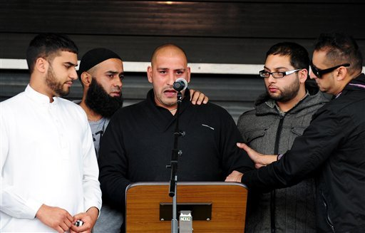Shazad Ali and Abdul Musavir's brother Abdul Qudoos, center, is supported by friends as he speaks at a peace rally a peace rally in Summerfield Park, Birmingham, England Aug. 14, 2011. (AP Photo/Rui Vieira/PA Wire)
