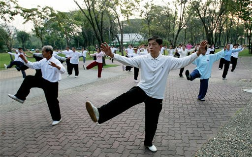FILE - In this Jan.18, 2011 file photo Thai-Chinese men and women take morning exercise by practicing Chinese martial arts at a park in Bangkok, Thailand.