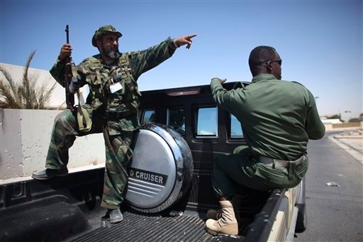 Rebel fighters talk to each other at the town of Brega, Libya, Monday, Aug. 15, 2011.