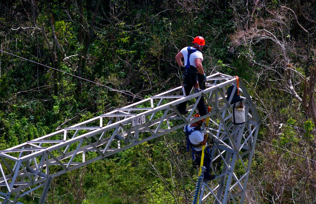 In this Oct. 15, 2017, file photo, Whitefish Energy Holdings workers restore power lines damaged by Hurricane Maria in Barceloneta, Puerto Rico. (AP Photo/Ramon Espinosa, File)
