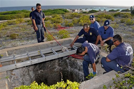 Firefighters and police officers conduct a search for Robyn Gardner, 35, of Frederick, Maryland, in a shaft of an old phosphate mine near Baby Beach, in the southern tip of Aruba, Friday Aug. 12, 2011.