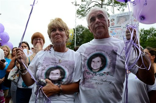 Cindy Anthony is comforted by George Anthony, right, during a memorial ceremony at the site where the body of their granddaughter Caylee Anthony was found on what would have been her sixth birthday in Orlando, Fla., Tuesday, Aug. 9, 2011.
