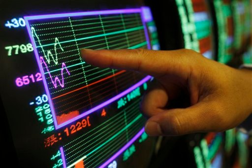 A securities manager points to a fluctuating stock indicator in Taipei, Taiwan, Wednesday, Aug. 17, 2011. (AP Photo/Wally Santana)