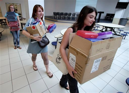 Seniors Holly O'Dell, left, Raycee Thompson, center, and Ashley Bilke carry donated school supplies to a classroom on the first day of school at a temporary high school in a converted big-box store in Joplin, Mo. (AP Photo/Charlie Riedel)