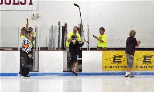 Nate Smith, 11, holds his stick up in jubilation after sinking a trick shot during a charity hockey game Thursday, Aug. 11, 2011, in Faribault, Minn.