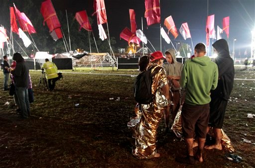 Music fans walk near to a collapsed tent after a storm swept through an open air music festival near Hasselt, about 50 miles (80 kilometers) east of Brussels, Belgium, Thursday, Aug. 18, 2011.