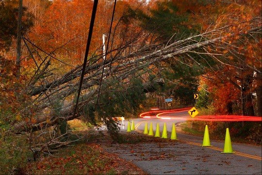A car leaves a trail of light as it passes under power lines weighed down by toppled trees in Freeport, Maine.