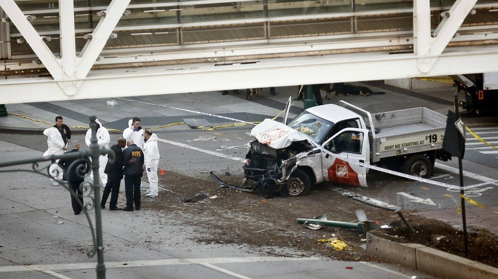 Authorities stand near a damaged Home Depot truck after a motorist drove onto a bike path near the World Trade Center memorial, striking and killing several people Tuesday, Oct. 31, 2017, in New York. (AP Photo/Bebeto Matthews)