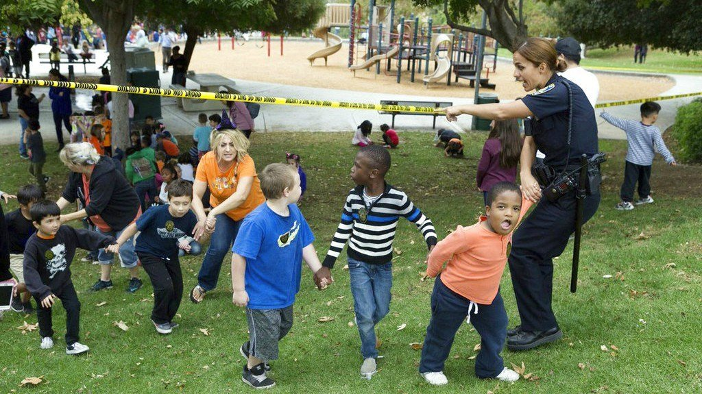Police help escort students to a nearby restroom as they wait to be released to parents after a man barricaded himself in a classroom at Castle View Elementary School in Riverside (Watchara Phomicinda/The Press-Enterprise via AP)