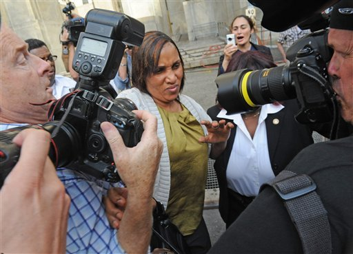 Nafissatou Diallo leaves Manhattan criminal court surrounded by a crush of photographers, Wednesday, July 27, 2011, in New York.