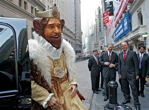 """FILE - In this May 18, 2006 photo, Burger King CEO John W. Chidsey, background center, watches as""""The King"""" mascot of Burger King Corp., arrives at the New York Stock Exchange in New York."""