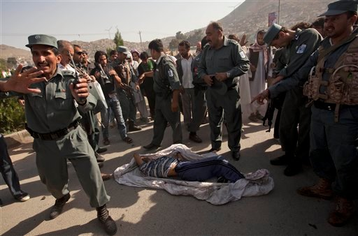 Afghan policemen stand near the dead body of suicide attacker outside The British Council in Kabul, Afghanistan, Friday, Aug. 19, 2011.