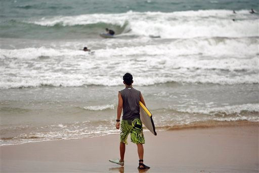 A surfer walks into the ocean as tropical storm Irene approaches to the island in Luquillo, Puerto Rico, Sunday, Aug. 21, 2011. The storm is packing winds of about 50 mph (85 kph) and tracking westward at 20 mph (32 kph). (AP)