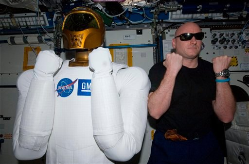 FILE - In this March 15, 2011 file photo provided by NASA, astronaut Scott Kelly, Expedition 26 commander, right, poses with Robonaut 2, the dexterous humanoid astronaut helper, in the Destiny laboratory of the International Space Station.