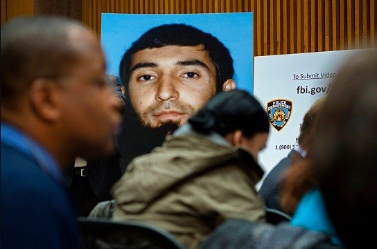 A photo of Sayfullo Saipov is displayed at a news conference at One Police Plaza .