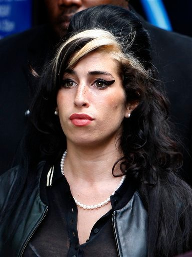 FILE - In this July 24, 2009 file photo, British singer Amy Winehouse leaves Westminster magistrates court in London after a judge acquitted her of assaulting a fan who asked to take her picture.