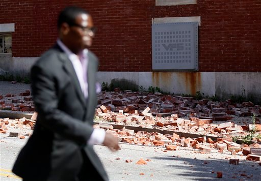 A man walks past bricks that fell off of a house once owned by the late Rep. Parren Mitchell, D-Md., after an earthquake was felt in Baltimore, Tuesday, Aug. 23, 2011. (AP Photo/Patrick Semansky)