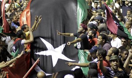 Libyans holding a huge flag celebrate overrunning Muammar Qaddafi's main compound Bab al-Aziziya in Tripoli, Libya, early Wednesday, Aug. 24, 2011. (AP Photo/Sergey Ponomarev)