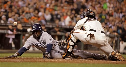 San Diego Padres' Orlando Hudson, left, slides to score past San Francisco Giants catcher Chris Stewart during the seventh inning of a baseball game Aug. 23, 2011, in San Francisco. (AP Photo/Ben Margot)