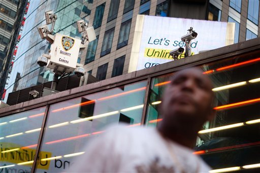 A pedestrian passes under the watchful eyes of surveillance cameras in Times Square in New York, Tuesday, Aug. 19, 2011.