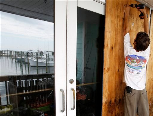 Jeremy Pickett boards the windows of a shopping store in Cape Hatteras, N.C. in preparation for Hurricane Irene on Wednesday, Aug. 24, 2011.
