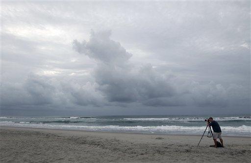 Cash Haggarty, of Washington, takes photos of the sunrise in Atlantic Beach, N.C., Thursday, Aug. 25, 2011. (AP Photo/Chuck Burton)