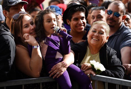 Sammi Corono-Lampa, 4, of Moreno Valley, Calif., a fan of the late singer Selena Quintanilla, sings songs by Quintanilla as she waits with her mother Patty, left, and her grandmother, Teresa, for a posthumous star ceremony on the Hollywood Walk of Fame on