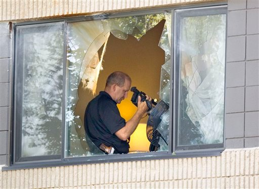 A Moscow police officer uses a video camera in a room rented by Ernesto Bustamante at the University Inn-Best Western in Moscow, Idaho, on Tuesday, Aug. 23, 2011.