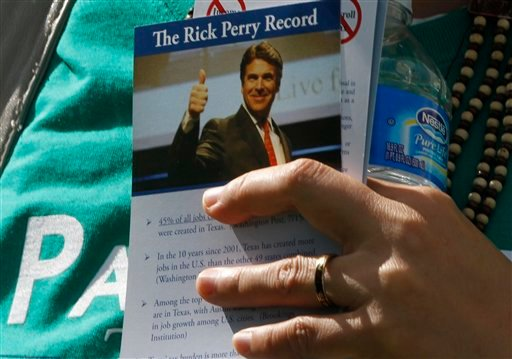 A supporter of Republican presidential candidate former Minnesota Governor Tim Pawlenty, not shown, holds a flyer about Texas Gov. Rick Perry at the Republican Party's Straw Poll in Ames, Iowa, Saturday, Aug. 13, 2011.