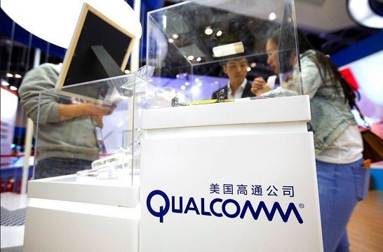 Visitors look at a display booth for Qualcomm at the Global Mobile Internet Conference (GMIC) in Beijing.