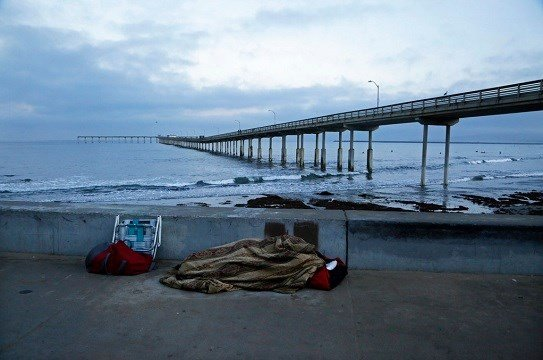 In this Sept. 28, 2017 photo, a person sleeps under a blanket on a beach near the Ocean Beach Pier in San Diego.
