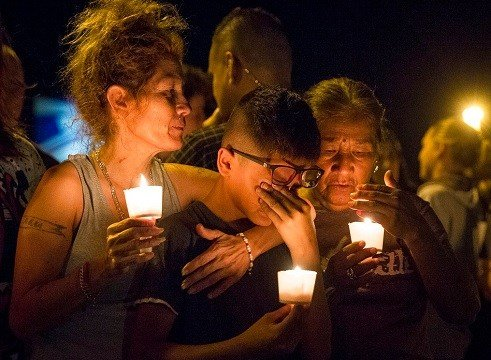 Mona Rodriguez holds her 12-year-old son, J Anthony Hernandez, during a candlelight vigil held for the victims.