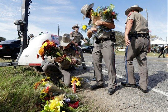 Law enforcement officials move flowers left at the scene of a shooting at the First Baptist Church of Sutherland Springs.