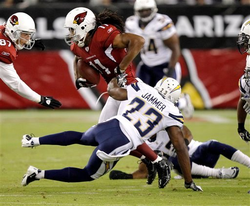 Arizona Cardinals' Larry Fitzgerald (11) breaks the tackle of San Diego Chargesr' Quentin Jammer (23) during the first half of an NFL preseason football game.