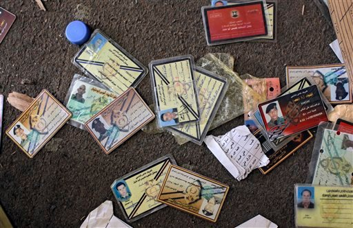 Military identification cards are seen on the floor in the headquarters of the elite military unit commanded by Moammar Gadhafi's son Khamis in Tripoli, LIbya, Sunday, Aug. 28, 2011. (AP Photo/Sergey Ponomarev)